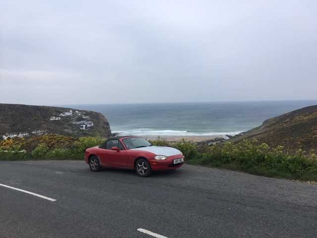 Small. scruffy red sports car on top of a hill overlooking a wild beach Cornish beach with waves crashing in.